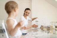 Happy mother and little daughter making a cake together in kitchen at home - DIGF06778