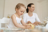 Mother and little daughter making a cake together in kitchen at home - DIGF06781