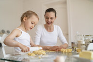Mother and little daughter with dough roll making a cake together in kitchen at home - DIGF06784