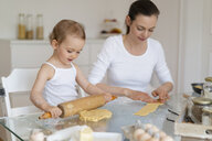Mother and little daughter with dough roll making a cake together in kitchen at home - DIGF06787