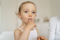 Little girl licking her finger while making a cake in kitchen at home - DIGF06790