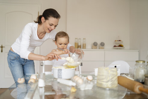 Mother and little daughter making a cake together in kitchen at home - DIGF06793