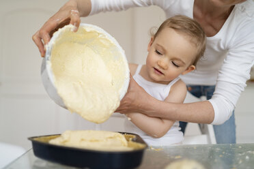 Mother and little daughter making a cake together pouring batter into baking pan - DIGF06796