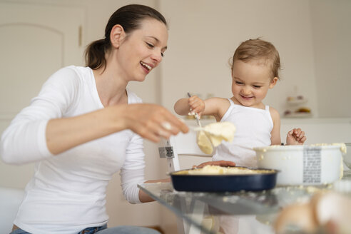 Happy mother and little daughter making a cake together in kitchen at home - DIGF06799