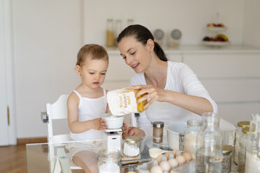 Mother and little daughter making a cake together in kitchen at home weighing flour - DIGF06802