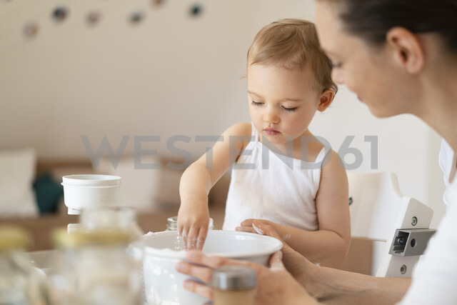 Mother and little daughter making a cake together in kitchen at home - DIGF06808 - Daniel Ingold/Westend61