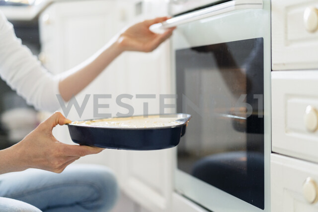 Close-up of woman putting cake batter into the oven - DIGF06820 - Daniel Ingold/Westend61