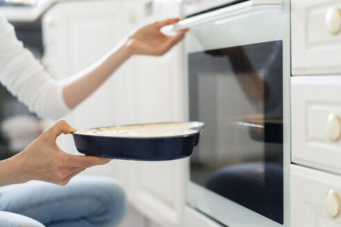 Close-up of woman putting cake batter into the oven - DIGF06820