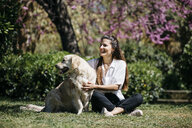 Happy woman sitting on meadow in city park with her Labrador Retriever enjoying sunlight - JRFF03153