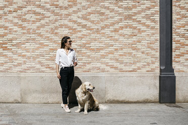 Woman and her Labrador Retriever waiting in front of patterned brick wall looking at distance - JRFF03156