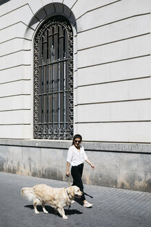 Spain, Barcelona, woman going walkies with her Labrador Retriever in the city - JRFF03159