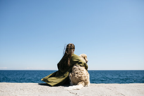 Back view of woman sitting besides her Labrador Retriever at quay looking at horizon - JRFF03162