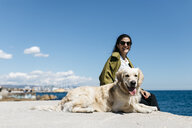 Happy woman sitting besides her Labrador Retriever at quay - JRFF03165