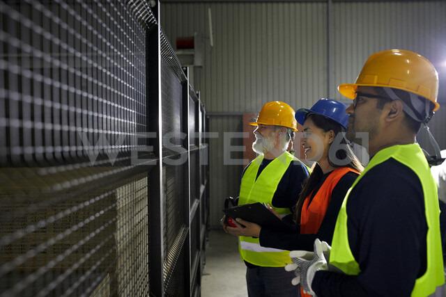 Smiling workers standing at grid in factory - ZEDF02233 - Zeljko Dangubic/Westend61
