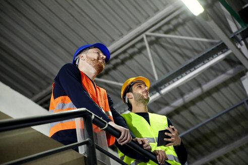 Two workers standing on upper floor in factory - ZEDF02236