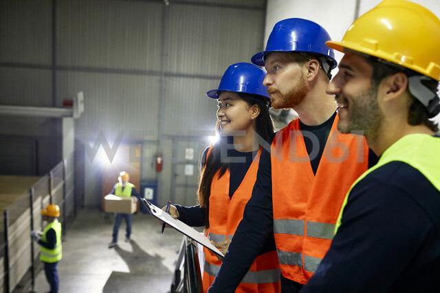 Two men and smiling woman in reflective vests in factory - ZEDF02239 - Zeljko Dangubic/Westend61