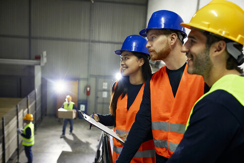 Two men and smiling woman in reflective vests in factory - ZEDF02239