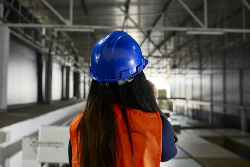 Rear view of female worker on the phone in factory warehouse - ZEDF02242