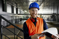 Portrait of happy worker in factory warehouse - ZEDF02245