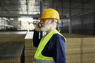 Mature worker on cell phone in factory warehouse - ZEDF02248