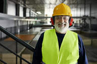 Portrait of smiling mature worker in factory warehouse - ZEDF02251