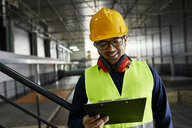Smiling worker holding clipboard in factory warehouse - ZEDF02254