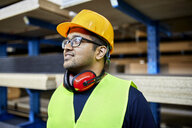 Portrait of smiling worker in factory warehouse - ZEDF02263