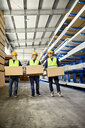 Three workers carrying boxes in factory warehouse - ZEDF02266