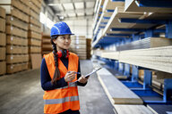 Smiling female worker with clipboard in factory warehouse - ZEDF02269