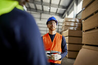Worker in factory warehouse holding tablet - ZEDF02278