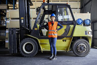 Portrait of confident female worker at forklift in factory - ZEDF02284