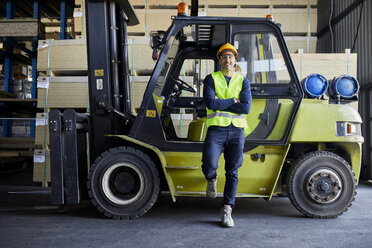 Portrait of confident worker at forklift in factory - ZEDF02287