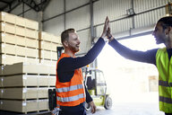 Happy colleagues in protective workwear high fiving in factory - ZEDF02293