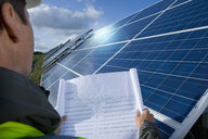 Close up of engineer looking at blueprint in front of solar panel - JUIF00877