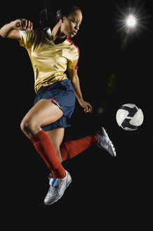 Mixed race soccer player kicking ball in mid-air - BLEF00074