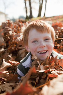 Caucasian boy playing in autumn leaves - BLEF00115