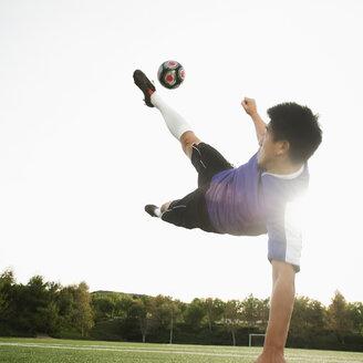 Asian soccer player in mid-air kicking soccer ball - BLEF00121