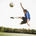 Caucasian soccer player in mid-air kicking soccer ball - BLEF00124
