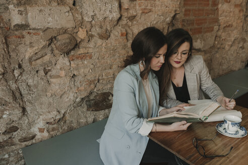 Two young women with notebook and book in a cafe - AHSF00127