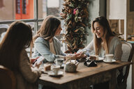 Three happy young women with cell phone meeting in a cafe - AHSF00130