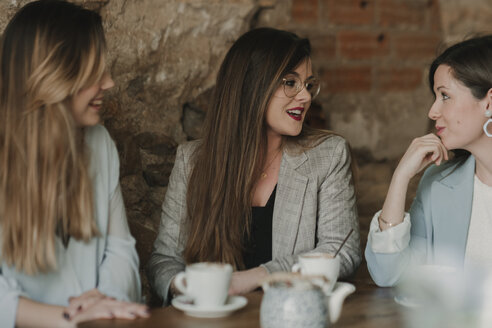 Three happy young women meeting in a cafe - AHSF00142