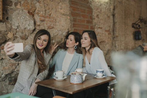 Spain, Aragon, Zaragoza, happy friends making selfie in coffee shop - AHSF00145