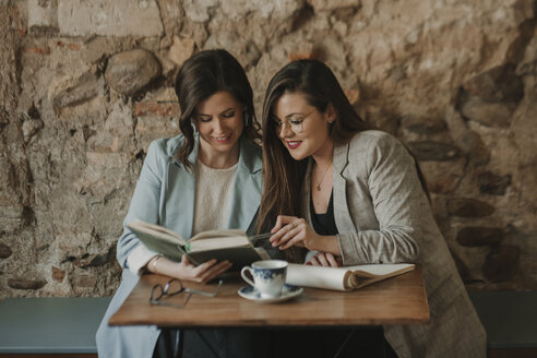Two young women with notebook and book in a cafe - AHSF00157