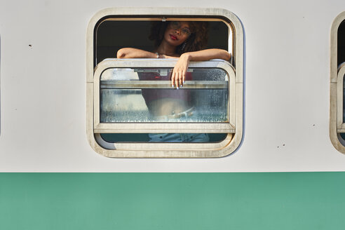 Woman looking out of train window - VEGF00043