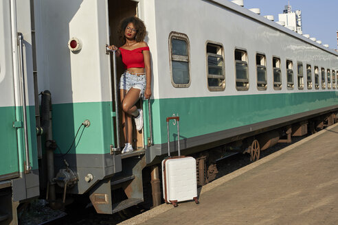 Woman with suitcase standing at the door of a train - VEGF00046