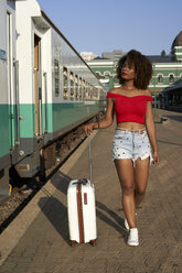 Woman walking with her suitcase at train station - VEGF00049