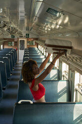 Young woman placing her suitcase in a train - VEGF00055