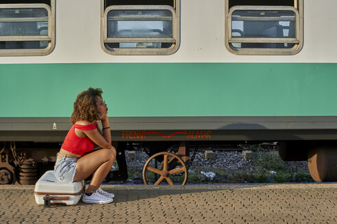 Woman sitting on her suitcase waiting for her train, Train Station, Moçambique, Maputo. - VEGF00061