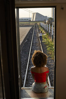 Woman sitting at the back door of a train looking at a woman on the tracks - VEGF00064