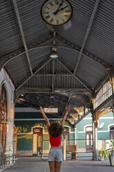 Happy woman under the clock at the train station - VEGF00070